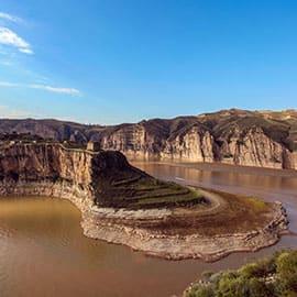 老牛湾位于山西省偏关县,是山西省和内蒙古自治区的交界处,以黄河为界,她南依山西的偏关县,北岸是内蒙古的清水河县,西邻鄂尔多斯高原的准格尔旗,是一个鸡鸣三市的地方。黄河从这里入晋,内外长城从这里交汇,晋陕蒙大峡谷以这里为开端,我国黄土高原沧桑的地貌特征在这里彰显。同时也有大河奔流的壮丽景观。老牛湾是长城与黄河握手的地方,是中国最美的十大峡谷之一。整个老牛湾旅游区由三湾一谷组成,分别是包子塔湾,老牛湾、四座塔湾和杨家川小峡谷。