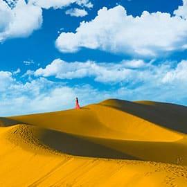 """敦煌鸣沙山是国家级重点旅游风景名胜区,处于库姆塔格沙漠边缘,与宁夏中卫县的沙坡头、内蒙古达拉特旗的响沙湾和新疆巴里坤哈萨克自治县境内的巴里坤镇同为中国四大鸣沙山。沙峰起伏,人们顺坡滑落,便会发出轰鸣声,称为""""沙岭晴鸣"""",为敦煌八景之一。"""