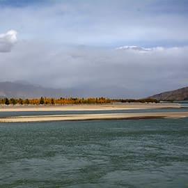 """拉萨河,藏语称吉曲,意为""""快乐河""""、""""幸福河"""",位于西藏中南部。拉萨河是拉萨市的母亲河,周末的时候,拉萨人喜欢约上三两好友驱车来到城南,在河边野炊、露营。每逢沐浴节,河边更是热闹非凡。也许你无法像当地人一样与拉萨河相处这么长时间,但也能在傍晚时分,到仙足岛、西藏大学附近的河边散步,欣赏落日与地平相触的美景。"""