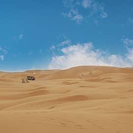 """沙坡头位于宁夏回族自治区中卫市城区西部腾格里沙漠的东南缘。集大漠、黄河、高山、绿洲为一处,具西北风光之雄奇,兼江南景色之秀美。有中国最大的天然滑沙场,有横跨黄河的""""天下黄河第一索"""",有黄河文化代表古老水车,有黄河上最古老的运输工具羊皮筏子,有沙漠中难得一见的海市蜃楼。可以骑骆驼穿越腾格里沙漠,可以乘坐越野车沙海冲浪,咫尺之间可以领略大漠孤烟、长河落日的奇观。"""