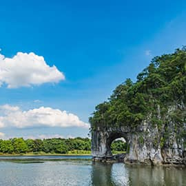 """象鼻山原名漓山,位于广西区桂林市内桃花江与漓江汇流处,山因酷似一只站在江边伸鼻豪饮漓江甘泉的巨象而得名,被人们称为桂林山水的象征。象山以神奇著称。其神奇,首先是形神毕似,其次是在鼻腿之间造就一轮临水明月,构成""""象山水月""""奇景。因此,象鼻山是桂林的城徽山,是桂林旅游的标志山。"""