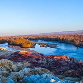 五彩滩位于阿勒泰布尔津县境内,地处我国唯一注入北冰洋的额尔齐斯河北岸的一、二级阶地上,是新疆最美的雅丹地貌,由于它色彩绚烂,形状缤纷而得名。经过千万年风蚀雨剥以及河水的冲刷,在几乎寸草不生的河滩上出现了红、绿、紫、黄、棕等鲜艳的色彩。