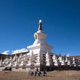 """稻城白塔又叫尊胜塔林,是稻城的门户, 由一个主塔和108个小塔组成,每天也都有人来转经。尊胜塔林的108个小塔内放置的是释迦牟尼佛祖,主塔内放置的是尊胜佛母。尊胜佛母,音:""""朗觉玛"""",乃长寿三尊之一,主长寿。"""