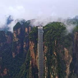 """""""乘百龙电梯,观张家界美景""""--百龙观光电梯位于张家界武陵源世界自然遗产核心景区,以""""世界上最高、载重量最大、运行速度最快的全暴露户外观光电梯""""三项桂冠独步世界,是从水绕四门跨越万丈绝壁通往袁家界连接天子山等机器凝固的垂直交通工具。"""