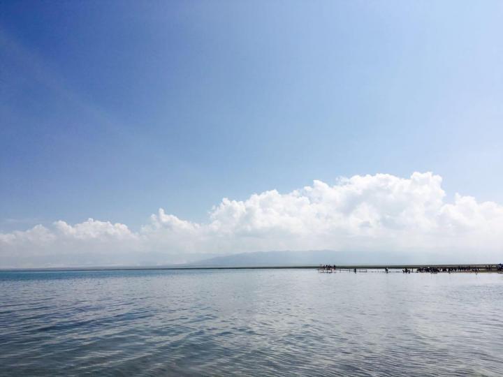 青海湖景区,青海湖真是太美了,特别多云的地方湖面就是灰色的 云层薄点的地方湖面就变蓝一点 湖很大,云很多,厚薄不一,被风吹得移动的很快,湖面的蓝色也跟着变幻。 水草丰富,牛羊埋头只顾吃。 公路右边是湖,左边是牧场和连绵起伏但是比较平缓的山峦