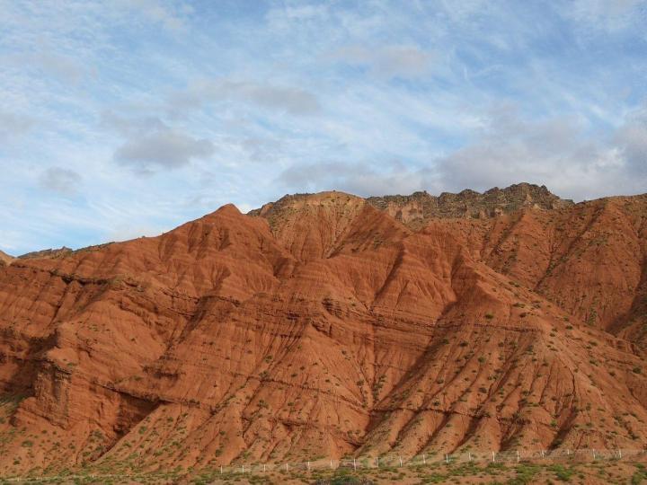 """库车大峡谷,门票费用相对还是算良心,加之就在公路旁边,所以游人基本都会在这里停留。 这里面的红褐色岩石是经过大自然亿万年的风刻雨蚀而形成。红褐色的山体群在阳光照射下,犹如一簇簇燃烧的火焰。 我觉得这里也可以算得上是""""火焰山""""了,实至名归"""