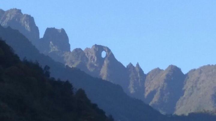 石月亮,石月亮就是高黎贡山上一个巨大的大理岩熔蚀而成的穿洞,下面是怒江峡谷。石月亮深百米,洞宽约40余米,高约60米,百里之外透着白云蓝天可见。