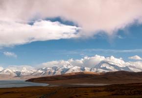 """纳木那尼峰被藏民称之为""""圣母之山""""或""""神女峰"""",与神山冈仁波齐峰南北遥遥相对,纳木那尼峰西面的山脊呈扇状由北向南排列,东面唯一的山脊被侵蚀成刃脊,十分陡峭,形成了高差近2000米的峭壁。西面的坡度则较为和缓,峡谷间倾泻着五条巨大的冰川,冰面上布满了冰裂缝和冰陡崖。夕阳低尽,纳木那尼峰神山魅影朦胧,晨曦洒落,重回庄严圣洁,很少有雪山能如此大气地展现它的全貌。"""