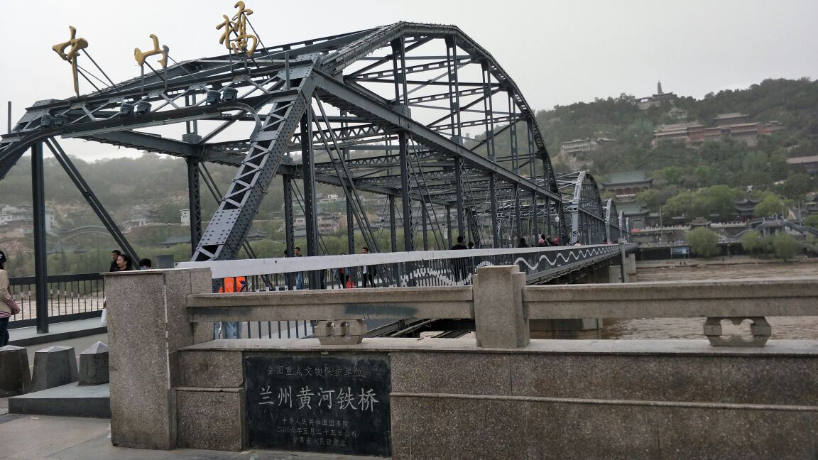 """黄河铁桥又名中山桥,是兰州最重要的地标建筑之一,铁桥长两百多米,宽约有七八米,保持了一百多年前修建时的黑色铁架桥身,十分古朴。铁桥南侧桥头处,有金色的""""中山桥""""三个大字,还有一块刻有""""黄河第一桥""""的古老石碑,每天都有很多游客到此合影,作为来过兰州的留念。这座铁桥修建于清朝末年,是当时黄河上架起的第一座常年通行桥,也被誉为""""天下第一桥""""。"""